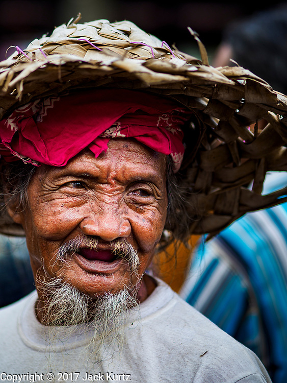 06 AUGUST 2017 - MENGWI, BALI, INDONESIA: A man in the livestock section of the Bringkit Market in Mengwi, about 30 minutes from Denpasar. Bringkit Market is famous on Bali for its Sunday livestock and poultry market. Hundreds of the small Bali cows are bought and sold there every week. Bali's local markets are open on an every three day rotating schedule because venders travel from town to town. Before modern refrigeration and convenience stores became common place on Bali, markets were thriving community gatherings. Fewer people shop at markets now as more and more consumers go to convenience stores and more families have refrigerators.     PHOTO BY JACK KURTZ