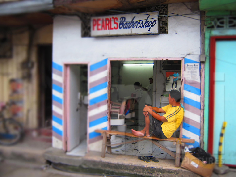 A man sits on a small bench in front of a barbershop while a barber cuts hair inside, Bohol Island, Phillippines, Southeast Asia