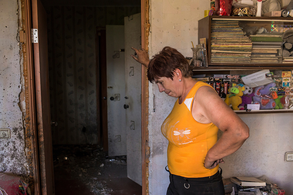 A woman whose apartment was heavily damaged by a suspected grad rocket strike on Tuesday, July 29, 2014 in Donetsk, Ukraine.