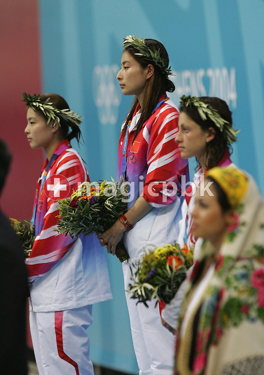 (from left) China's Minxia Wu, compatriot Guo Jingjing, Russian Yulia Pakhalina and a flower girl (far right) listen to the national anthem of China during the podium ceremony of the women's 3m Springboard finals of the Athens 2004 Olympic Games at the Aquatic Center, Thursday 26 August 2004. Guo Jingjing won the gold and Minxia Wu the silver medal, Yulia Pakhalina bronze.    (Photo by Patrick B. Kraemer / MAGICPBK)