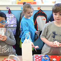 Lauren Wood   Buy at photos.djournal.com<br /> Ashtyn Creely, center, passes out valentines to her classmates Finley Thomas, left, and Mitchell Rhea during the Valentine's Day party Friday afternoon in Carol Elliott's first grade classroom.