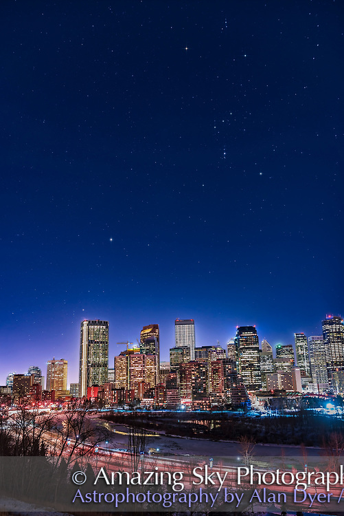 An urban nightscape of the constellations of Orion and Canis Major over the skyline of Calgary on January 18, 2018, on a very clear and moonless winter night, allowing stars to show up fairly well despite the light pollution. Sirius is above the Bow Tower building at left. <br /> <br /> I shot this from Crescent Road on the north bank of the Bow River, with Orion nearly due south as high as it could get. So this is a real scene, not a faked composite with a sky shot someplace else or at some other time layered in. <br /> <br /> However, the view was helped by the use of a NISI Natural Night light pollution filter on the lens which helped filter out the yellow emission lines from sodium vapour lights, and rendered the sky a more pleasing blue tint (this is not from moonlight). <br /> <br /> The faintest stars are about magnitude 7.5, not bad from a city site, though this was a very clear, haze-free night, the sky factor. <br /> <br /> In addition, the sky is a longer single exposure of 10 seconds at f/2.5 and ISO 400 (which brought out the stars more but overexposed the skyline), while the skyline is a stack of 4 x 3-second exposures at f/2.8 and ISO 400 (to better expose for the bright lights). This composited accommodated the huge range of brightness of the scene. something like an HDR blend. <br /> <br /> I shot this with the 24mm Sigma Art lens and Nikon D750. <br /> <br /> I added the star diffraction spikes for artistic effect using Astronomy Tools actions.