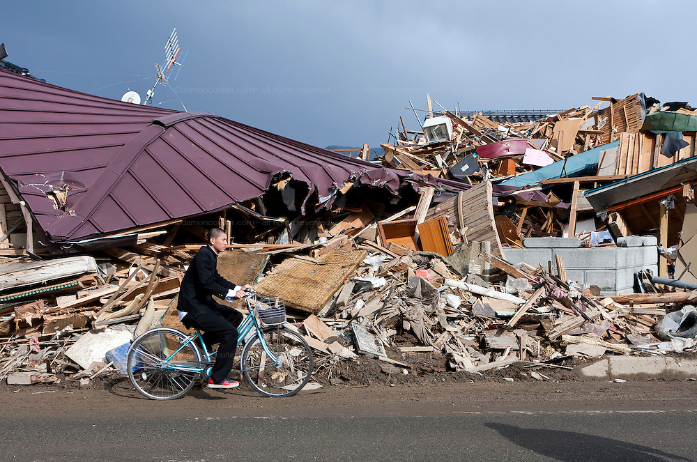 A Japanese high school boy in uniform rides a bicycle in front of the effects of the tsunami in Ofunato, Iwate, Japan. March 17th 2011