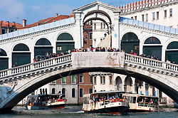Vaporetti or public waterbuses passing below famous Rialto Bridge in Venice Italy