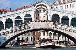 Vaporetti or public waterbuses passing below famous Rialto Bridge in Venice Italy
