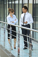 Businessman conversing with businesswoman at corridor