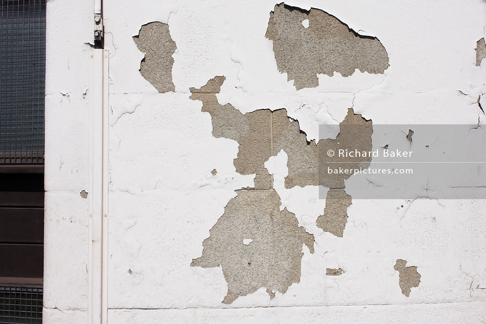 Like the continents on a world map, abstract peeling white painted wall in Bermondsey, London.