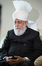 Image ©Licensed to i-Images Picture Agency. 27/06/2014. Morden, United Kingdom. British Muslims condemn Isis at Friday prayers in LND Mosque. Fifth Caliph and worldwide head of the Ahmadiyya Muslim Community, Mirza Masroor Ahmad answer questions from a journalist at the Baitul Futuh mosque in Morden - the largest mosque in western Europe - regarding the extremism in UK and the ISIS group which he condemns. Baitul Futuh Mosque. Picture by Daniel Leal-Olivas / i-Images