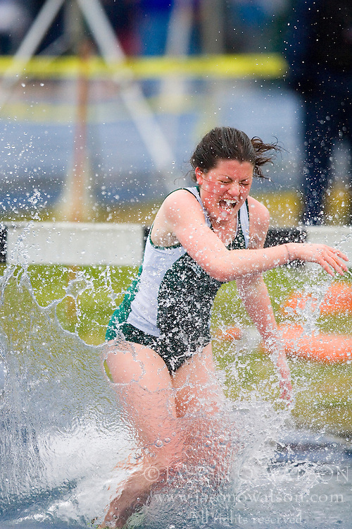 A competitor in the women's 3000m steeplechase reacts after splashing into the water hazard.  The Virginia Cavaliers Track and Field team hosted the 2007 Lou Onesty/Milton G. Abramson Invitation at Lannigan Field at the University of Virginia on April 14, 2007.