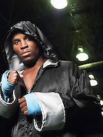 Boxer wearing robe with hood up clenching fists portrait