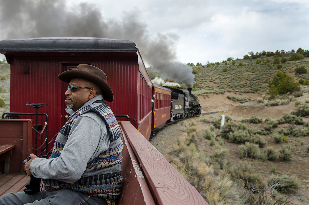 Train passengers take in the scenery from an open carriage on the Cumbres & Toltec.