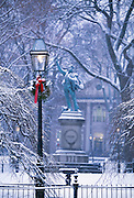 USA, Newport, RI - Snow covered trees and a gas lamp dressed with a wreath and ribbon for Christmas in Washington Square Park. The Oliver Harzard Perry statue stands in the background.