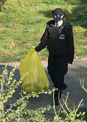 © Licensed to London News Pictures. 05/10/2014. Brentford, UK . A police officer holds a yellow bag. Police remove the body of Arnis Zalkains from Boston Manor Park today 5th October 2014. The body of a man, believed to be Latvian killer Arnis Zalkalns, was found in Boston Manor Park, Brentford, almost six weeks after the schoolgirl Alice Gross vanished. Arnis Zalkalns was prime suspect in the murder of 14-year-old Alice Gross.. Photo credit : Stephen Simpson/LNP