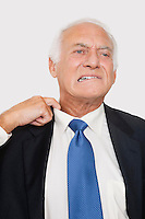 Elderly businessman holding collar feeling uncomfortable against white background