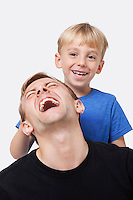Portrait of young boy playing with father over white background