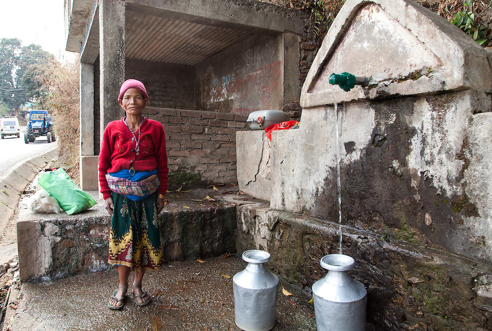 A Nepali woman poses for a photograph at a roadside public water tap