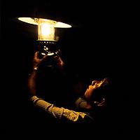 Man fixes light in the dark, Ban Pak Ou, Luang Phrabang, Laos