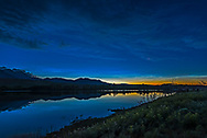 Noctilucent clouds glowing low in the north and reflected in unsually calm waters of the Waterton River at the Maskinonge picnic area in Waterton Lakes National Park, Alberta on June 17, 2018. There was no wind this night, rare for Waterton. <br /> <br /> This is a high dynamic range stack of 5 exposures from dark to light, blended with Adobe Camera Raw. Taken with the Nikon D750 and Sigma 20mm lens. Additional contrast enhancement applied using Zone System Express 5 Photoshop extension and &ldquo;Enhanced Contrast&rdquo; function.