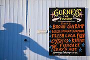 Shop sign for Gurneys Fish Shop - fresh shrimp, salmon, oysters, kippers - in Burnham Market in North Norfolk, UK