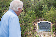 Tom Beard looks at a historical marker for the natural spring on his ranch near Alpine, Texas on June 17, 2015. (Cooper Neill for The Texas Tribune)