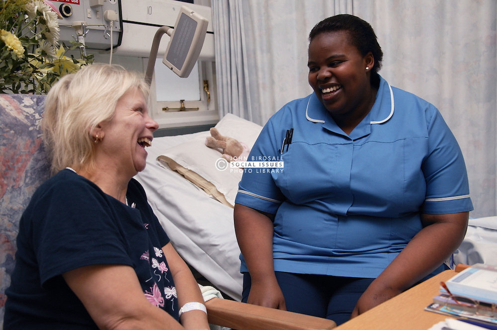 Cardiology Staff Nurse chatting to patient on the Ward who is awaiting a triple bipass operation,