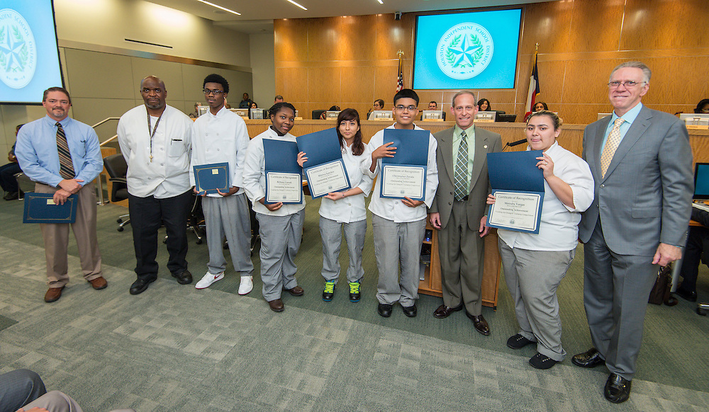 Greg Meyers and Ray Danilowicz, right, pose for a photograph with culinary students from Barbara Jordan High School during a meeting of the Houston ISD Board of Trustees meeting, September 11, 2014.