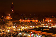 Place Djemaa el Fna at night with Koutoubia Mosque in the background.
