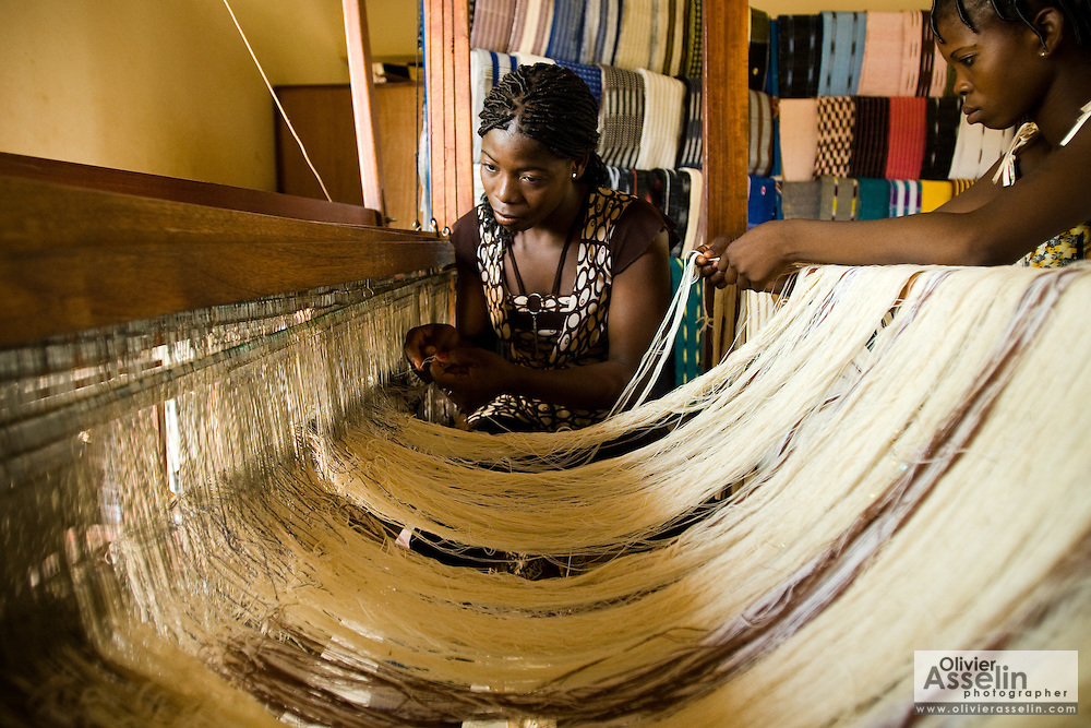 Women use traditional looms to weave textile at the Village Artisanal de Ouagadougou, a cooperative that employs dozens of artisans who work in different mediums, in Ouagadougou, Burkina Faso, on Monday November 3, 2008.