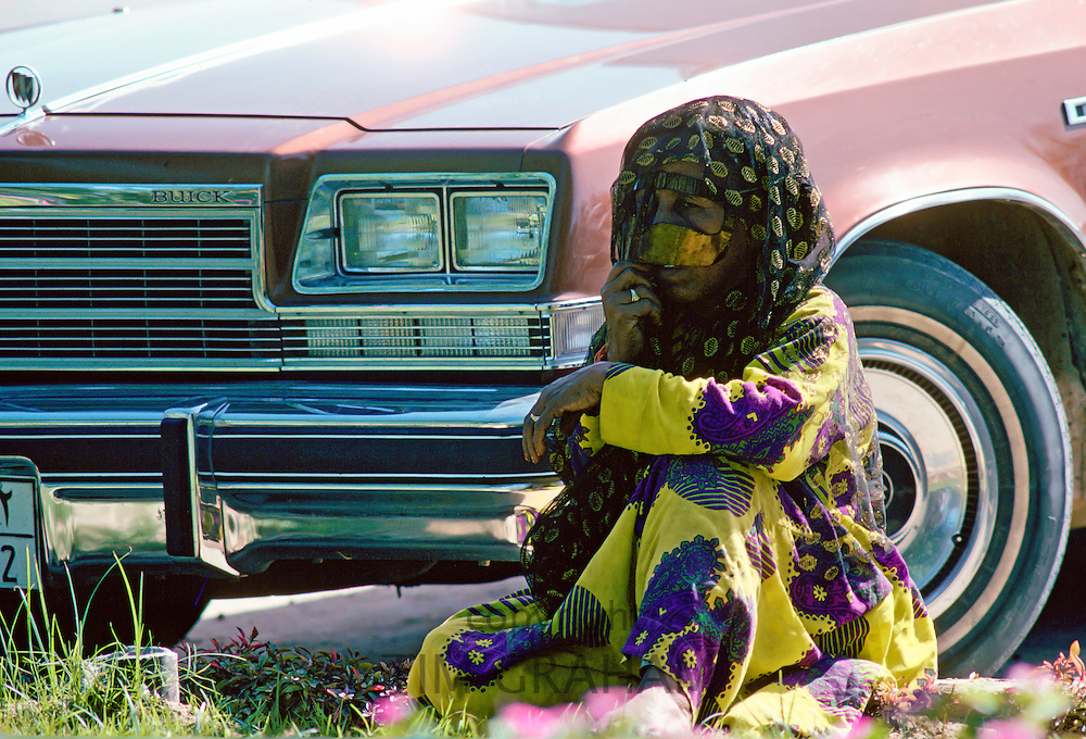 A Bedouin woman wearing traditional headgear and asaba headcovering, sits by a Buick car , Abu Dhabi