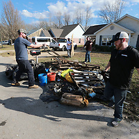 James Wells, right, and others help ruined items from the home of Robert Langford in the Willow Creek subdivision in Saltillo.