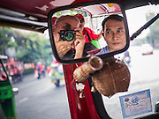 "10 DECEMBER 2012 - BANGKOK, THAILAND: Photojournalist JACK KURTZ photographs  a protest for constitutional reform from inside a ""tuk-tuk"" (three wheeled taxi) on Ratchadamnoen Avenue in Bangkok Monday. The Thai government announced on Monday, which is Constitution Day in Thailand, that will speed up its campaign to write a new charter. December 10 marks passage of the first permanent constitution in 1932 and Thailand's transition from an absolute monarchy to a constitutional monarchy. Several thousand ""Red Shirts,"" supporters of ousted and exiled Prime Minister Thaksin Shinawatra, motorcaded through the city, stopping at government offices and the offices of the Pheu Thai ruling party to present demands for a new charter.      PHOTO BY JACK KURTZ"