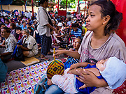 04 SEPTEMBER 2017 - BANGKOK, THAILAND: Poor people from riverfront communities in Bangkok wait for a food distribution to start at Chaomae Thapthim Shrine. About 1,000 people came to the shrine for the annual food distribution. Staples, like rice and cooking oil, are donated to the shrine throughout the year and donated to poor people from the communities around the shrine. Food distributions like this are a tradition at Chinese shrines in Bangkok and a common way of making merit for the people who donate the staples.     PHOTO BY JACK KURTZ