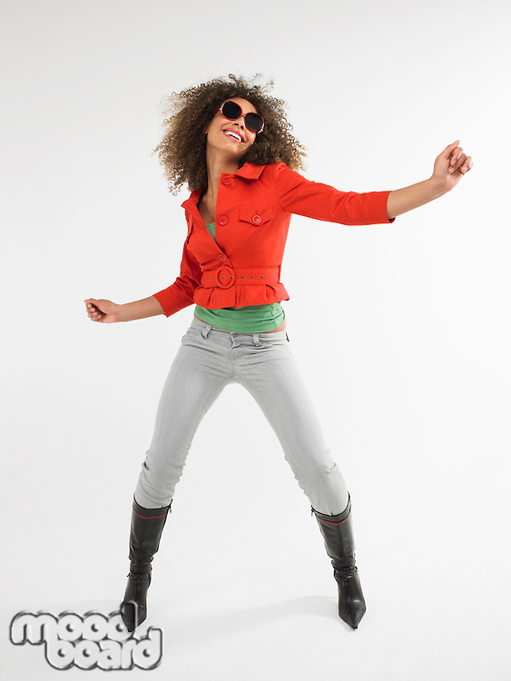Woman with curly hair wearing sunglasses dancing  in studio