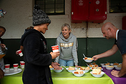 """Jo Swart serves lunch to the resident homeless at a the temporarily extended Night Shelter, in Somerset West, Western Cape, on April 21. When South Africa went into lockdown on March 27, """"Night Shelter jumped into help homeless outside our organization,"""" said Swart, who is the chairperson of the organization and a senior pastor in Somerset West. <br /> """"This crisis has highlighted how much the local NPO does,"""" she says. <br /> The government had organized a central tent facility in sea-side Strandfontein, and was bussing people there. But in the end, many people who had been gathered in the Strand- and Somerset West for a ride to Strandfontein ended up here at Night Shelter instead. For some, the bus never came. And others were sent back here from Strandfontein, Swart explained. In the end, the facility, there, reached capacity. <br /> SW Night Shelter normally provides temporary shelter, and other support services, to adults living on the streets who are committed to reintegration. This """"new"""" building, an old school, was meant to be for women and children. Now, about 70 people, including families, are living here together during lockdown. <br /> """"I didn't envision being in this situation during lockdown,"""" she says. """"This [shelter] was supposed to be for women and children.""""<br /> People who live on the streets have their own way of life and some use drugs, says Swart. So being in lockdown, with a hot meal and roof over one's head, isn't necessarily a luxury, she explains. """"Many homeless people here in lockdown are coming off drugs,"""" said Swart. """"We had hot cross buns, muffins… We are trying to keep them happy with food. They are eating huge amounts of food because they are coming off drugs.""""  PHOTO: EVA-LOTTA JANSSON"""