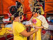 """26 NOVEMBER 2014 - BANGKOK, THAILAND:  Chinese opera performers put on their costumes at the Chow Su Kong Shrine in the Talat Noi neighborhood of Bangkok. Chinese opera was once very popular in Thailand, where it is called """"Ngiew."""" It is usually performed in the Teochew language. Millions of Chinese emigrated to Thailand (then Siam) in the 18th and 19th centuries and brought their culture with them. Recently the popularity of ngiew has faded as people turn to performances of opera on DVD or movies. There are about 30 Chinese opera troupes left in Bangkok and its environs. They are especially busy during Chinese New Year and Chinese holidays when they travel from Chinese temple to Chinese temple performing on stages they put up in streets near the temple, sometimes sleeping on hammocks they sling under their stage.     PHOTO BY JACK KURTZ"""