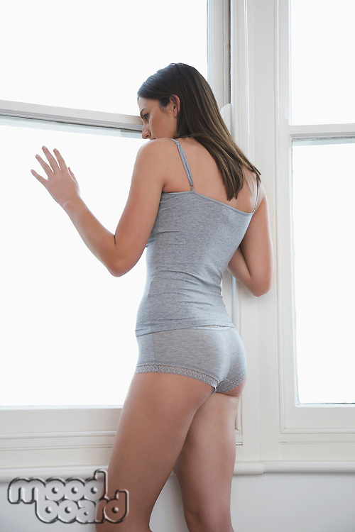 Young woman in underwear looking out of bedroom window