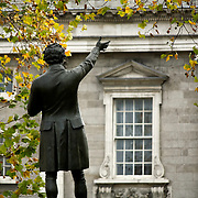 A statue infront of the fascade of trinity college, With Autumn leaves overhead, and the windows of Trinity College in the Background