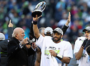 (L-R) Football analyst and former Pittsburgh Steelers quarterback Terry Bradshaw watches as Seattle Seahawks quarterback Russell Wilson (3) holds up the NFC Championship Trophy after the Seattle Seahawks win the NFL week 20 NFC Championship football game against the Green Bay Packers on Sunday, Jan. 18, 2015 in Seattle. The Seahawks won the game 28-22 in overtime. ©Paul Anthony Spinelli