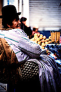 An elderly woman dressed in traditional attire sells plum juice on the streets of La Paz, Bolivia.