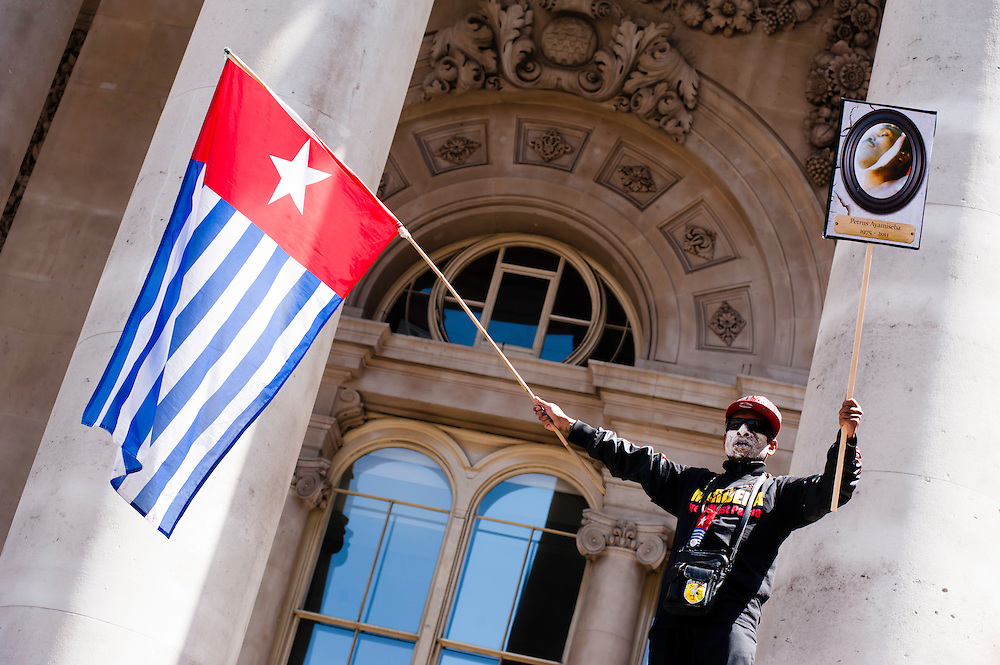 London, UK - 15 June 2012: an activist holds a  West Papua flag and a sign reading 'Petrus Ayamiseba 1975-2011'  in front of the London royal Exchange during the Carnival of Dirt. Petrus Ayamiseba was a PT Freeport Indonesia (PTFI) worker who was shot dead on Oct. 10 during a clash with the police.