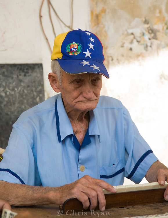 Elderly man playing dominos on a sidewalk, Havana, Cuba