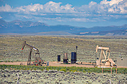 An oil fracking well site and pumpjacks pulling crude out of a remote high plain near Walden, Wyoming.