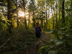Mature woman hiking on narrow footpath in forest, Baden-Wuerttemberg, Germany
