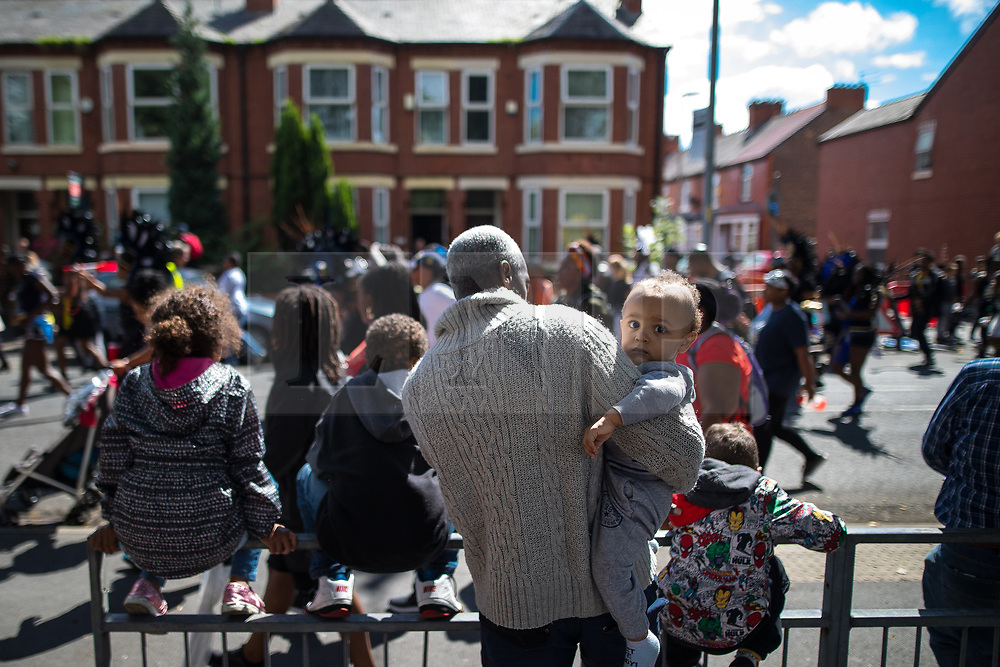 © Licensed to London News Pictures . 12/08/2017 . Manchester , UK . People gather along the route to watch the parade . The annual Caribbean Carnival J'Ouvert Parade through Moss Side in South Manchester . The 2017 theme is Bacchanal . There is concern in the community following the stabbing to death of Sait Mboob during a mass fight which saw several seriously hurt on Tuesday night (8th August 2017) . Photo credit : Joel Goodman/LNP