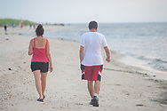 People walk along the beach as the sun sets Thursday, July 18, 2019 on the Delaware Bay in Villas, New Jersey. (Photo by William Thomas Cain/CAIN IMAGES)