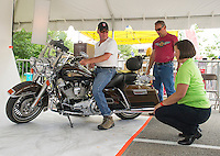 Don Thibodeau Having served in the Army 82nd Airborne / Paratrooper gets lined up for a portrait with Stacy Pearsall from the Veteran's Portrait Project at Laconia Harley Davidson Friday afternoon.   (Karen Bobotas/for the Laconia Daily Sun)