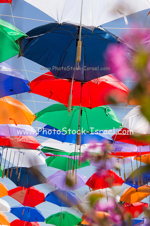 Colourful umbrellas strung up together on a blue sky background