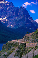 A Red Bus rounds a corner in Glacier National Park, Montana