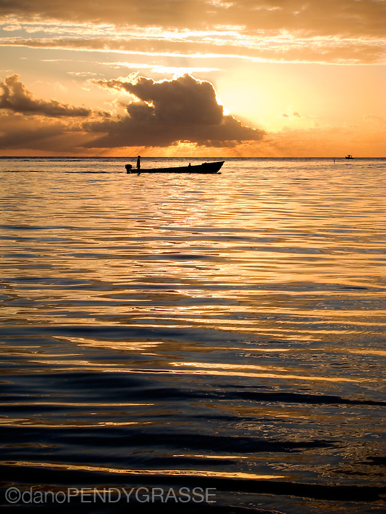A fishing skiff makes its way home as the sun sets behind a cloud in Roatan, Honduras.