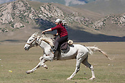 Woman galloping during a kiss chase (Kyz-Kuumai) competition at a traditional Kyrgyz horse games festival. Bosogo jailoo, Naryn province, Kyrgyzstan.